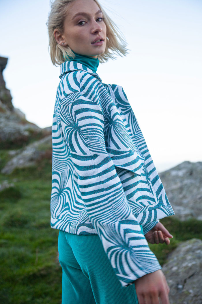 Model Wearing Turquoise And White Swirl Pattern Jacket And Turquoise Trousers