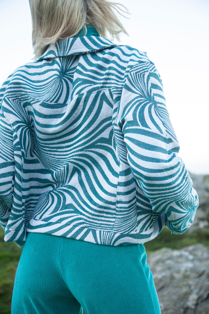Rear view of model wearing turquoise and white swirl pattern jacket and turquoise trousers