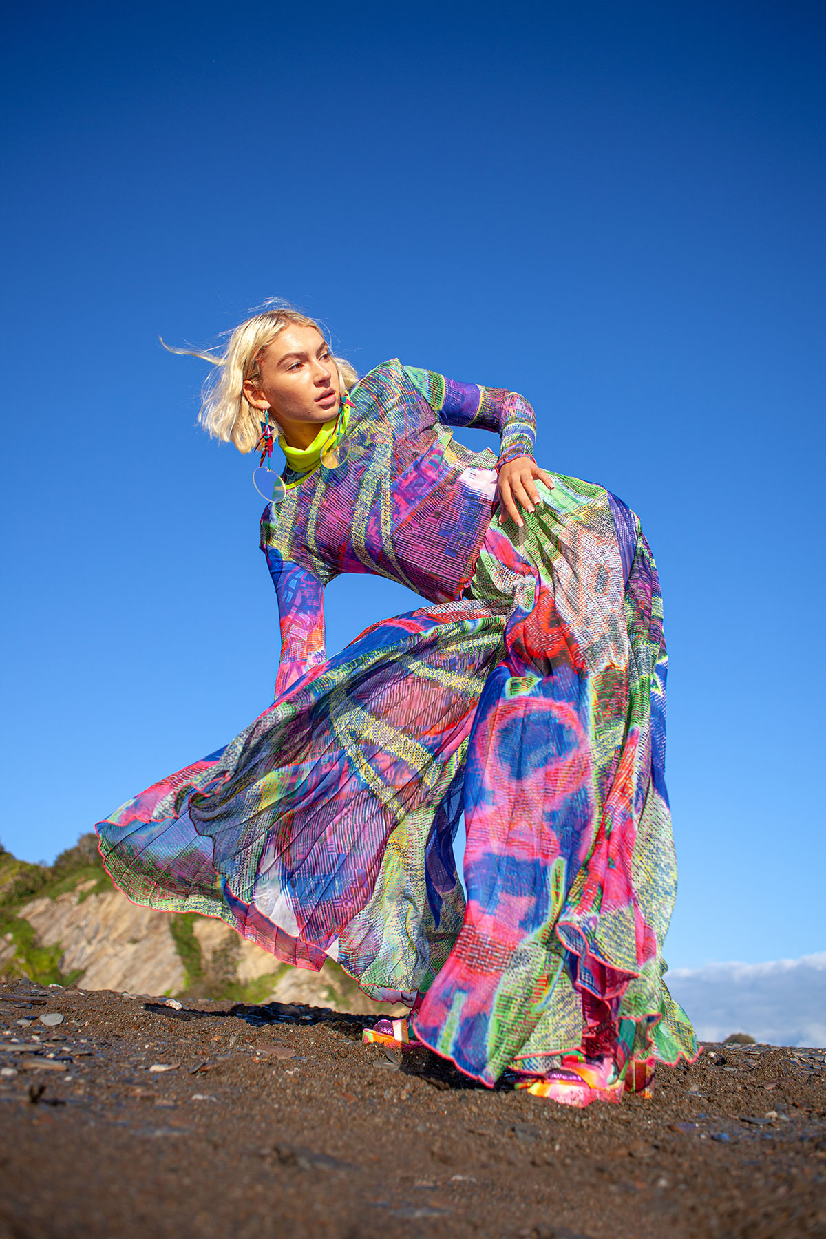 Blonde woman wearing multi-coloured coloured dizzydaze dress with blue sky behind