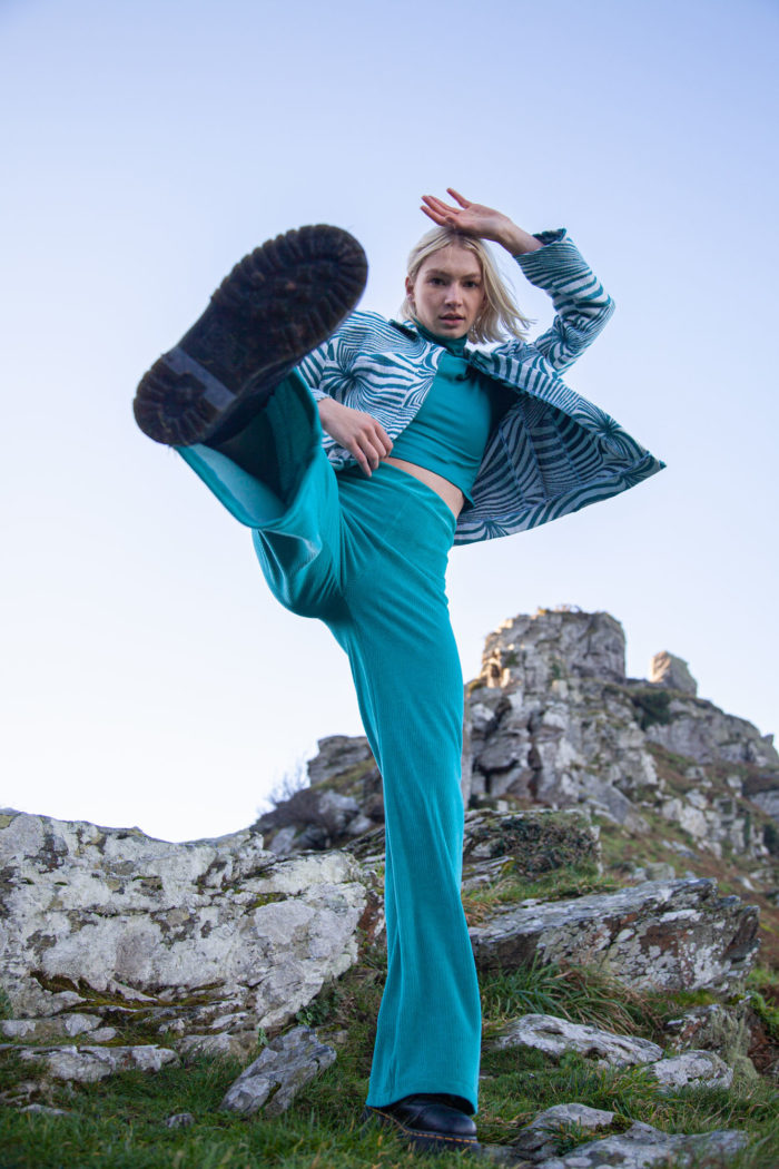 Model Wearing Turquoise Trousers And Top And Patterned Jacket