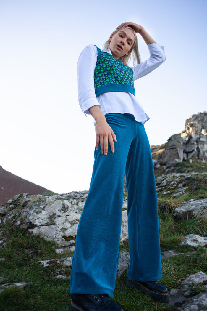 Model wearing Blue Trousers with Patterned Cropped Tank Top and White Blouse