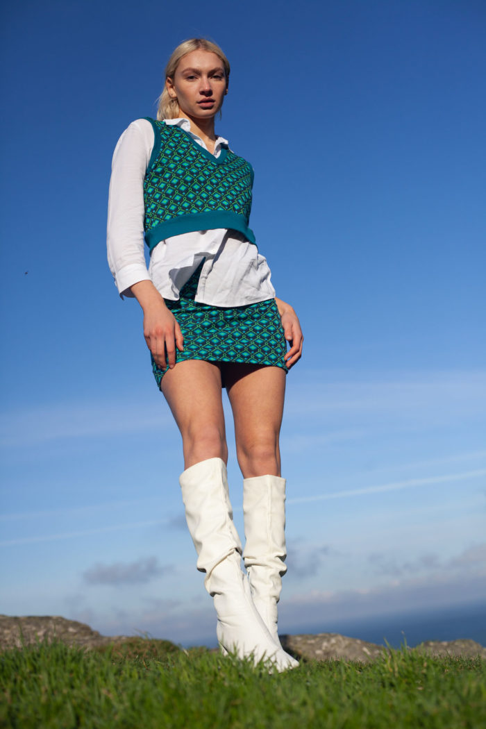 Model Wearing Blue Green Patterned Cropped Tank Top And Matching Skirt With White Blouse And Long White