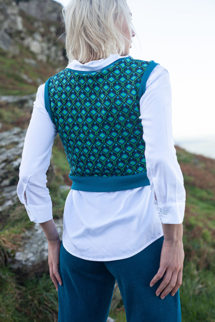 Model Wearing Blue Green Patterned Cropped Tank Top With White Blouse And Blue Velour Trousers