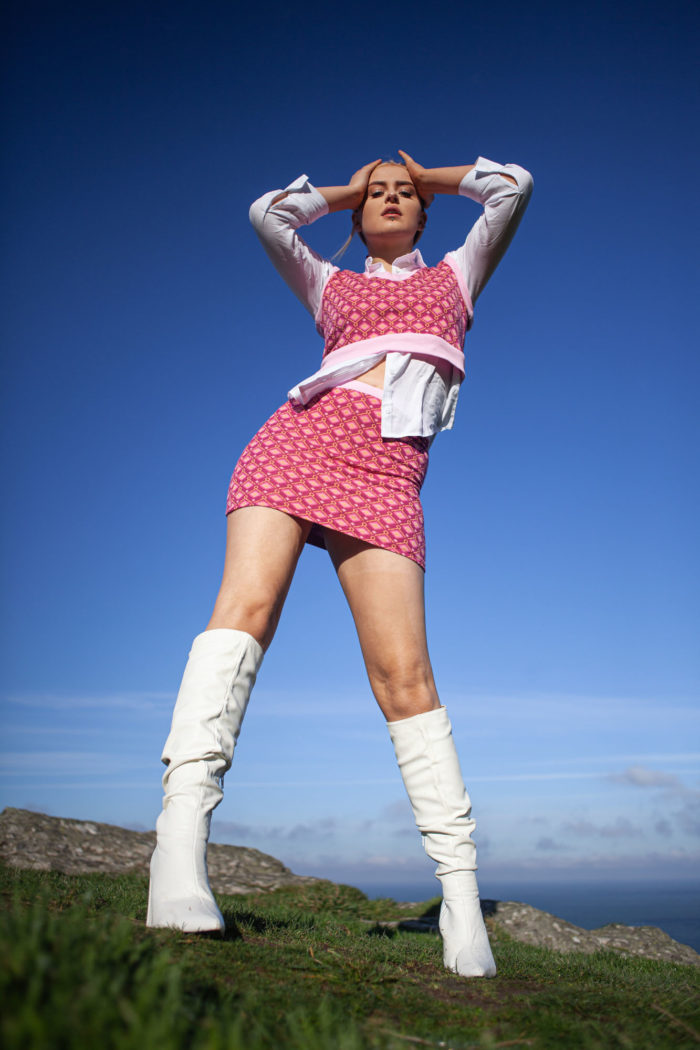 Model Wearing Pink Orange Patterned Cropped Tank Top And Matching Skirt With White Blouse Long And White Boots