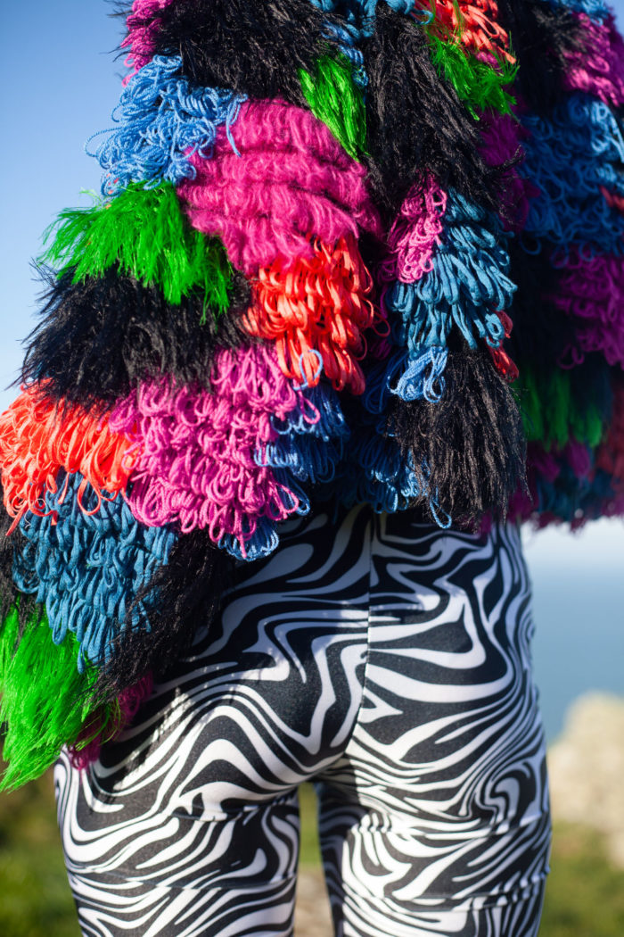 Rear View of Multi-coloured Textured Cardigan with Black and White Shorts